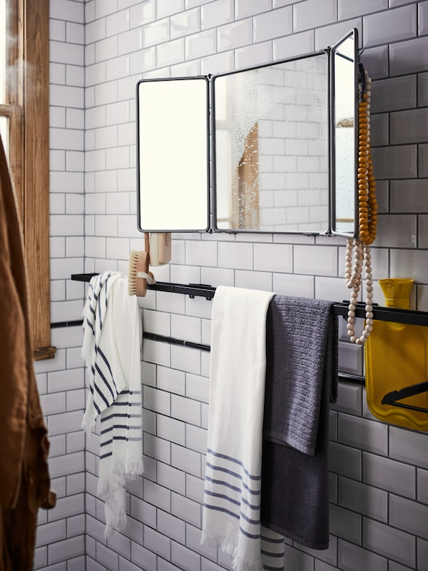 SKOGSVIKEN black towel rail with towels against a white tile bathroom wall with a SYNNERBY tri-fold mirror above.