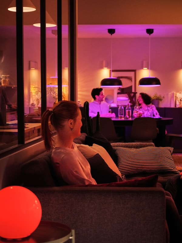An open living-room setting with three persons seated in sofas in soft light from several smart lighting sources.