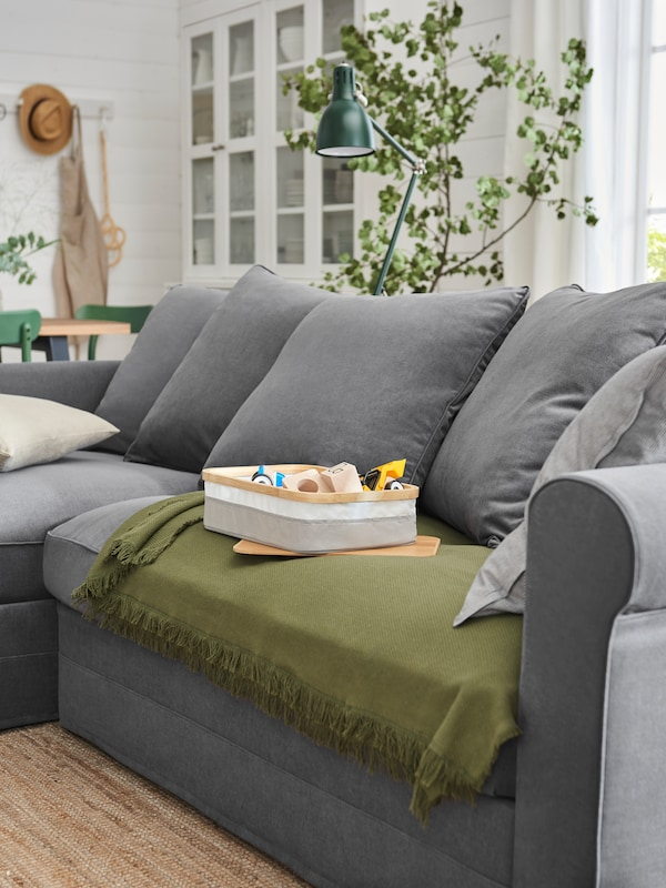 GRÖNLID three-seat sofa with chaise longue, in Ljungen medium grey, with a dark-green ODDRUN throw.