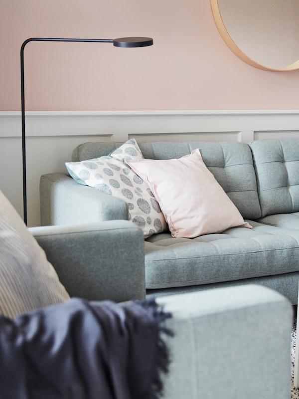 Ein Sofa mit Kissen steht an einer Wand. Neben ihm befindet sich eine Standleuchte und vor ihm ein Sessel mit Kissen und Plaid.