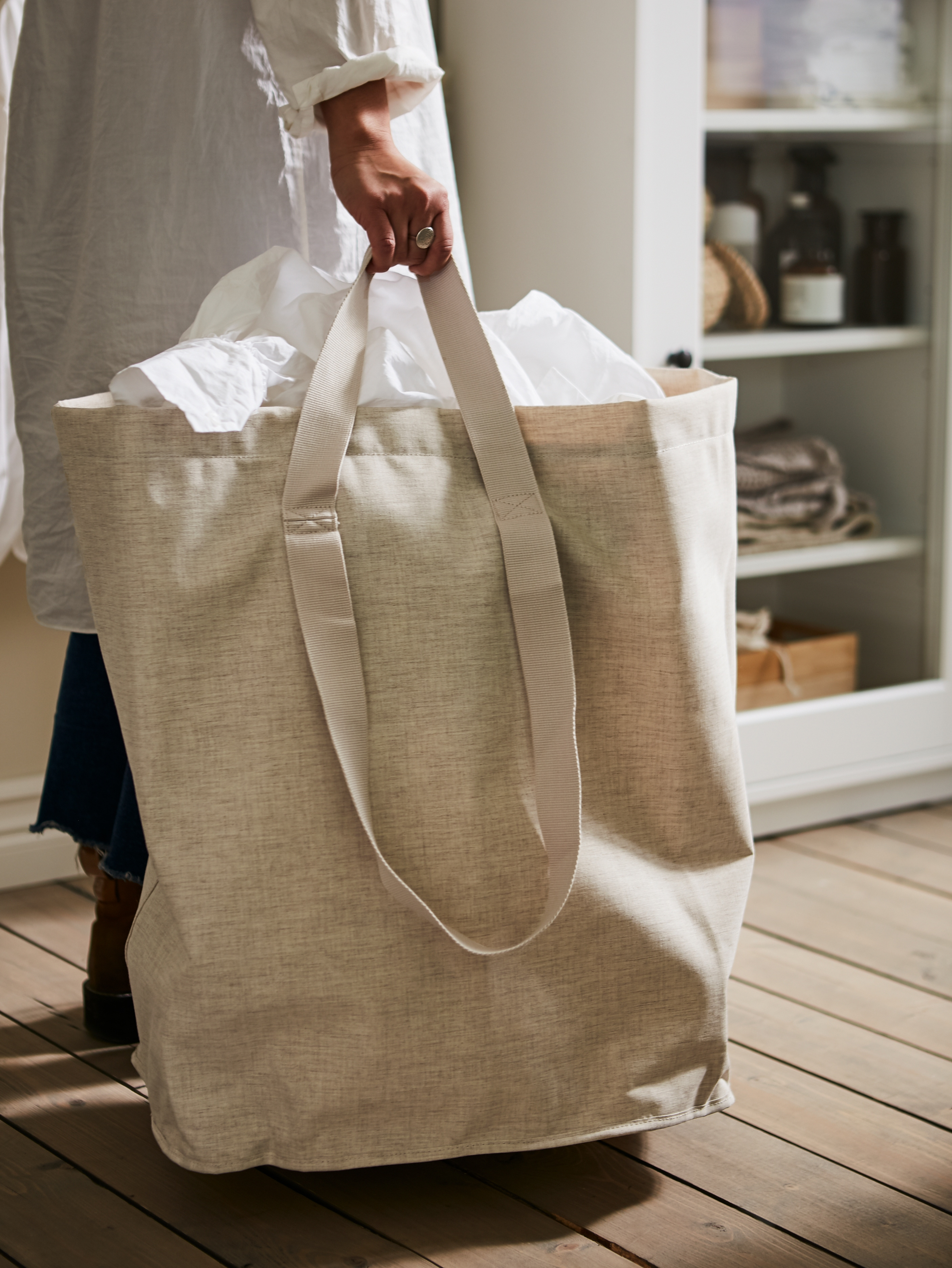A woman walking across a wooden floor holding a beige PURRPINGLA laundry bag filled with white textiles.