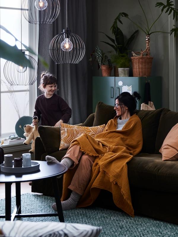 Frau sitzt eingekuschelt in einer VALLKRASSING Decke auf einem FÄRLOV Sofa. Die Tochtser steht neben dem Sofa. Auf einem Couchtisch brennen Kerzen.