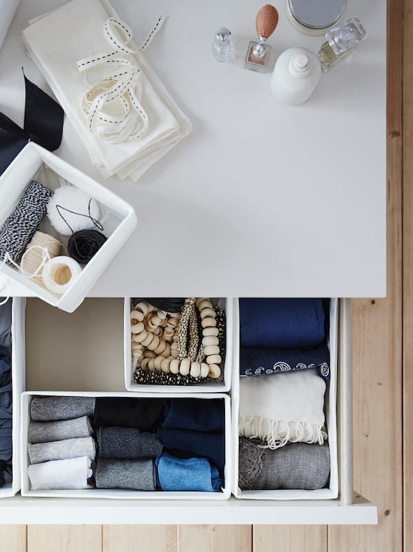 SKUBB boxes sit inside the open drawer of a chest of drawers. One SKUBB box sits on top along with other items.