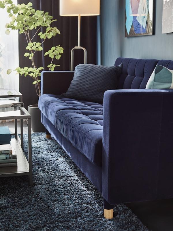 Modrá pohovka LANDSKRONA, za ktorou je stena sobrazmi. Naboku pohovky je izbová rastlina slampou apred pohovkou sú dva sklené stolíky.