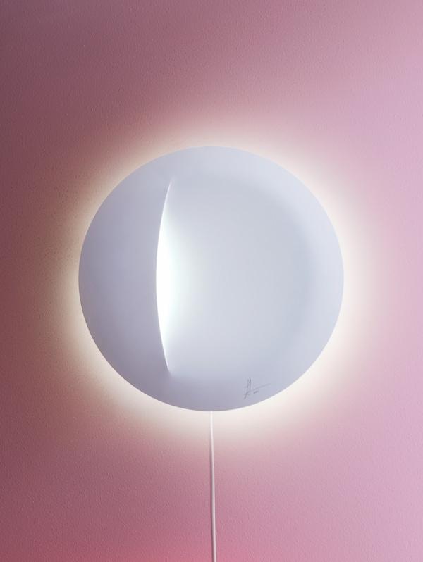 Bijela IKEA ART EVENT 2021 lampa u obliku diska dizajn je Sabine Marcelis i visi na rozom zidu te pruža blagu svjetlost.