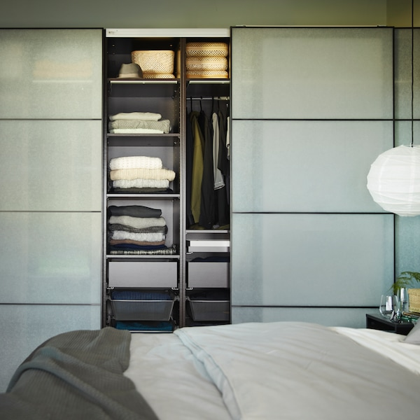 A PAX wardrobe with one sliding door open showing shelves and a rail filled with clothes, by a bed with ÄNGSLILJA bed linen.