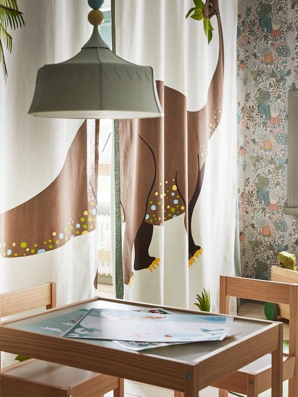 JÄTTELIK gordijnen met een LÄTT kindertafel en stoelen ervoor, en een TROLLBO hanglamp boven de tafel.