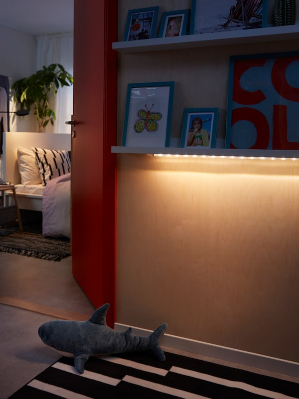 Space outside a bedroom where an LED lighting strip softly lights up the floor from underneath a picture ledge.