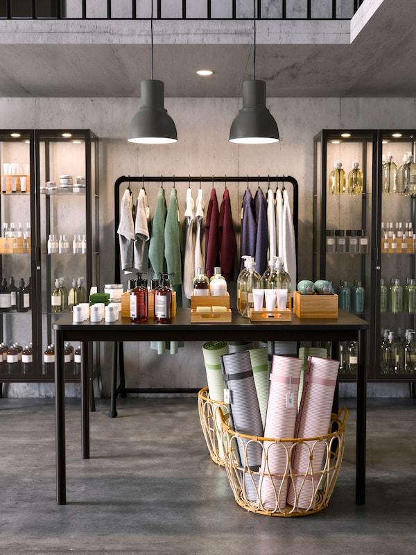 Geschäftsraum, in dem im Hintergrund Kleidung an einer Stange zu sehen ist. Davor ist ein Tischdisplay mit verschiedensten Produkten positioniert.