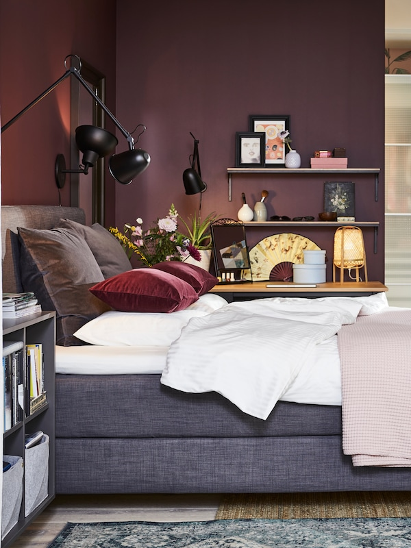 DUNVIK kontinentalseng med hvitt sengetøy og puter med grå og vinrøde SANELA putetrekk samt tre svarte vegglamper.