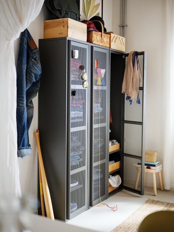 A corner of a room with three high, grey IVAR cabinets with mesh doors filled with clothes, and storage boxes on top.