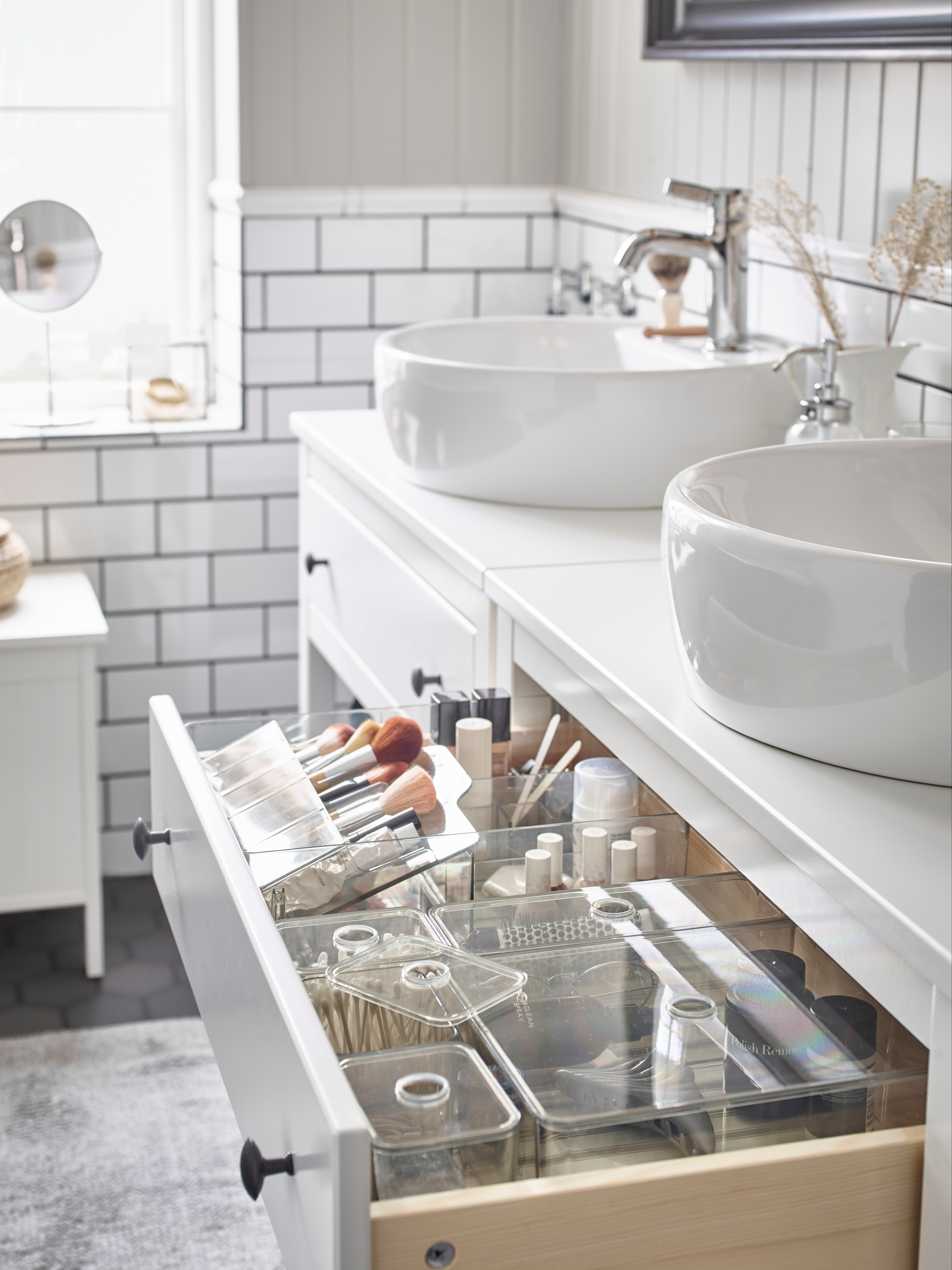 The drawer of a white wash-stand is open to show five GODMORGON clear, smoked boxes with lids holding bathroom accessories.