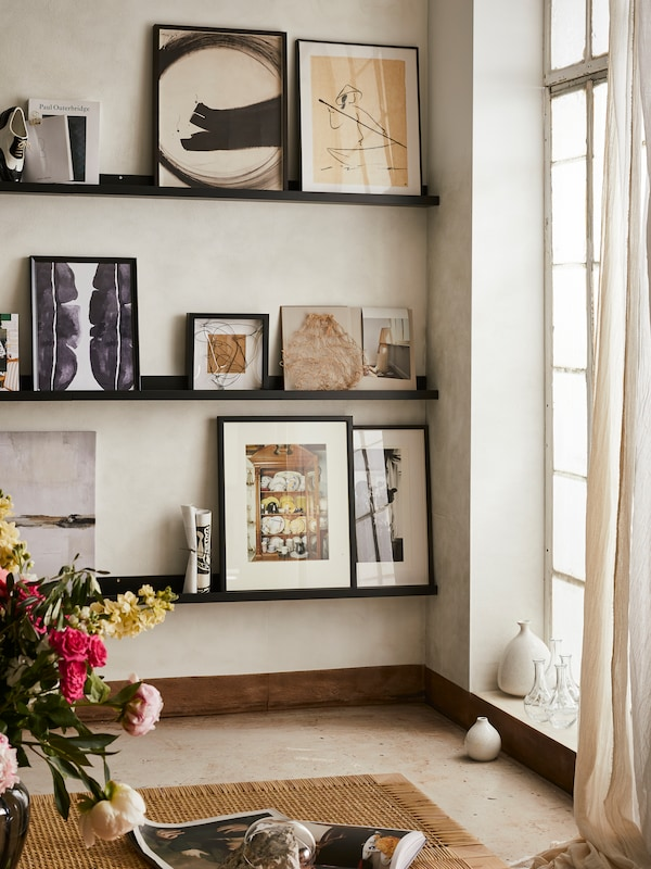 3 horizontal rows of MOSSLANDA black picture ledges on a wall displaying various prints inside black frames next to a window.