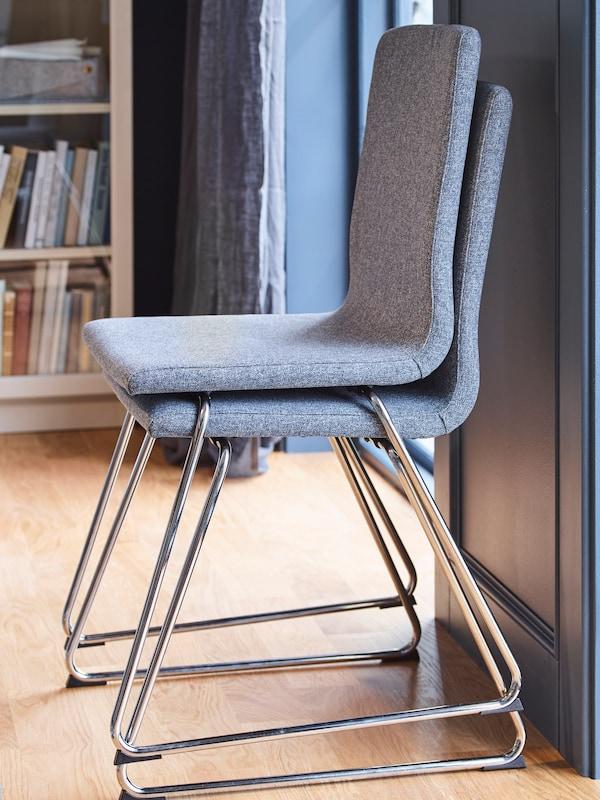Due sedie VOLFGANG cromate impilate l'una sull'altra. Sullo sfondo, una libreria BILLY piena di libri.