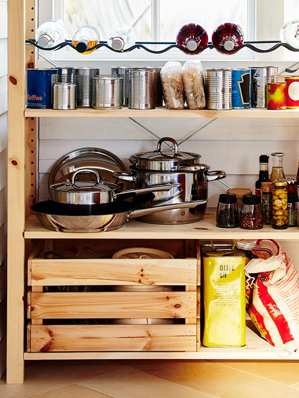 A raw pine shelf filled with neatly stored pots and pans, and cans of food.