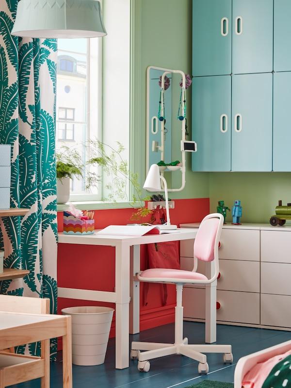 PÅHL skrivebord, en lyserød/hvid juniorstol, en hvid affaldsspand og en hvid bordlampe ved et vindue.