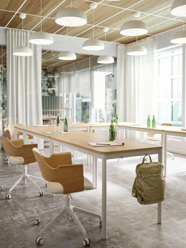 Stühle aus hellem Holz, weiße Leuchten und Tische aus hellem Holz mit Haken an der schmalen Tischseite. An einem der Haken hängt ein grüner Rucksack.