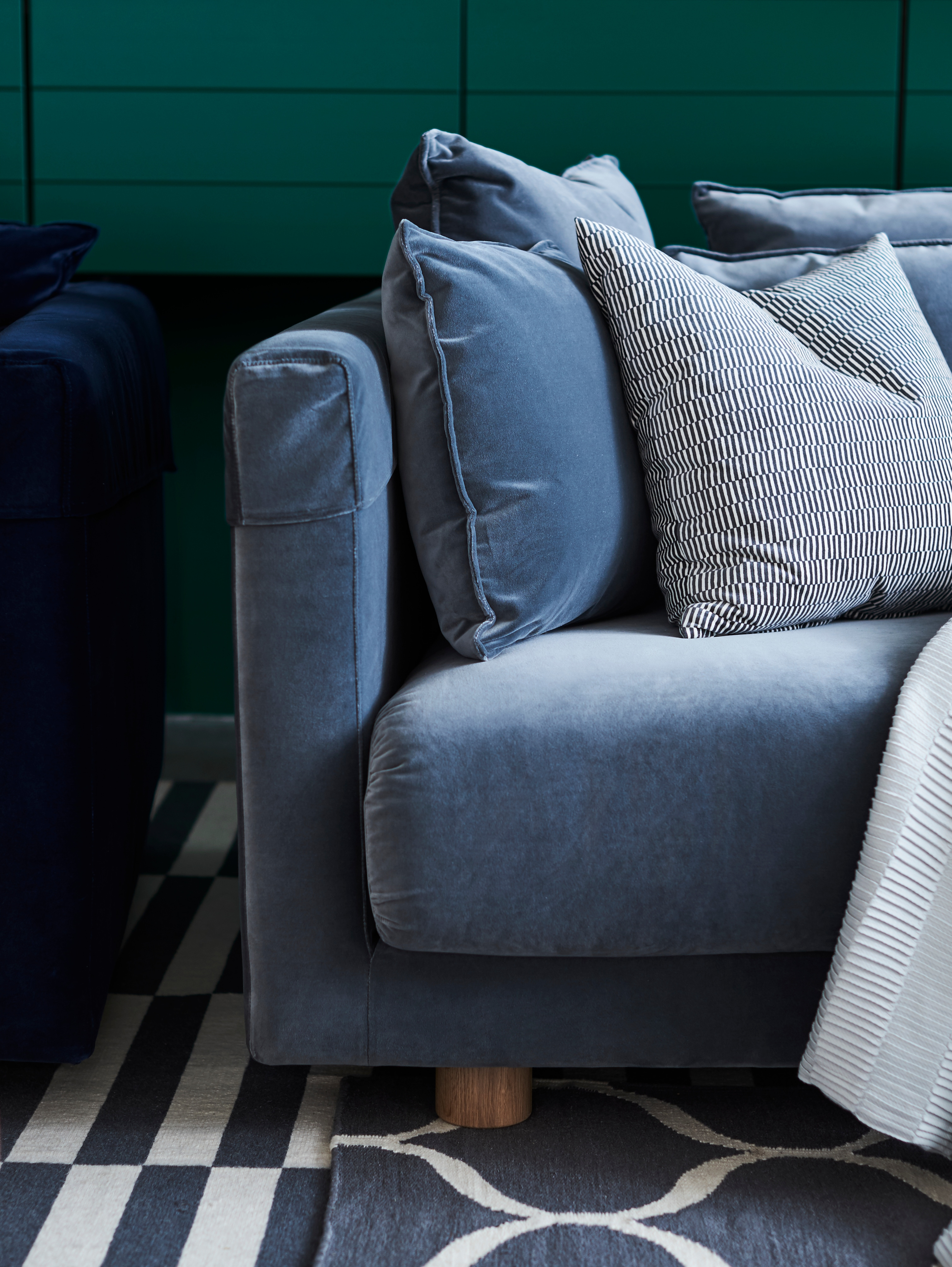 A close-up of the lefthand corner of a velvet STOCKHOLM 2017 three-seat sofa in Sandbacka dark grey with lots of cushions.