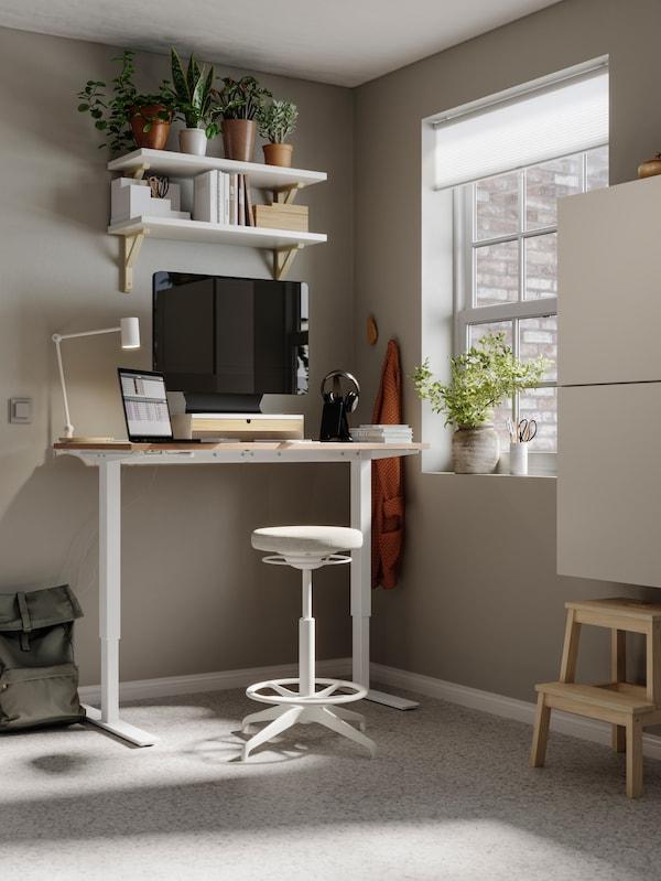 Un spațiu de lucru de acasă cu pereți bej, un birou SKARSTA la care se poate lucra așezat/în picioare și unități de depozitare BESTÅ.