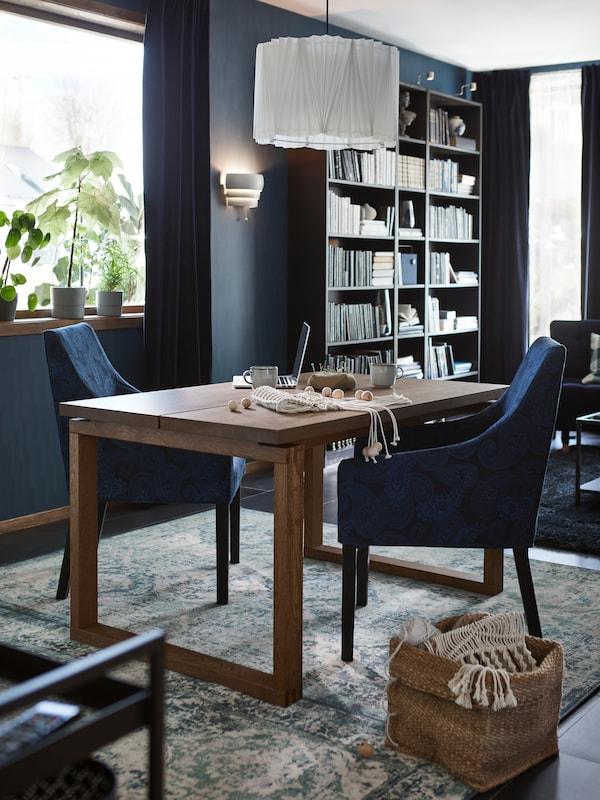 Drevený stôl sdvomi modrými jedálenskými stoličkami. Na stole je laptop aumelecké potreby, zatiaľ čo nad ním je biela závesná lampa.