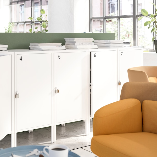 White lockable cabinets with numbers on them, with stacks of paper on the top surface, beside two dark yellow armchairs.