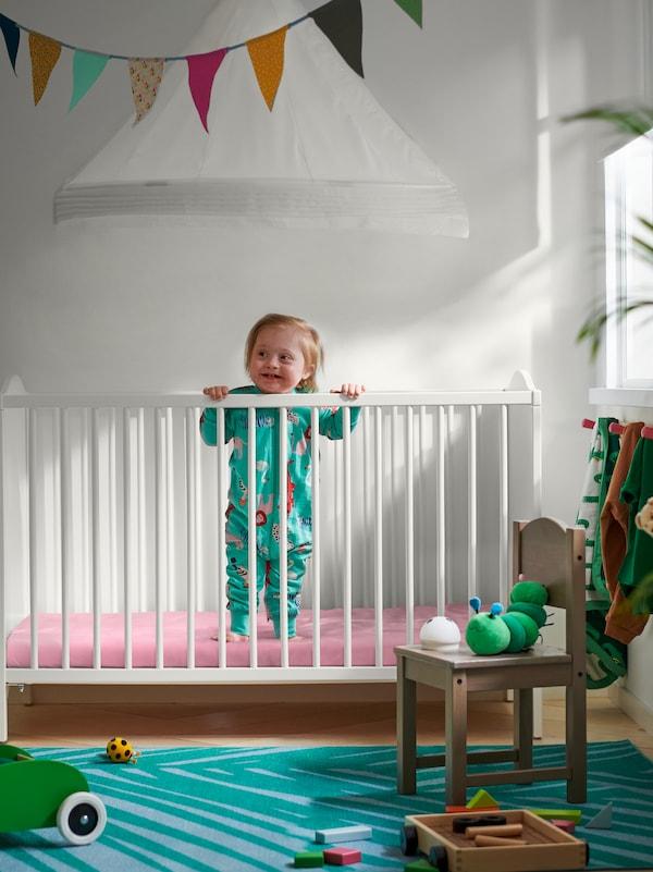 Un copil stă într-un pătuț SMÅGÖRA. Material multicolor suspendat deasupra, pe tavan, și un scaun pentru copii SUNDVIK în față.