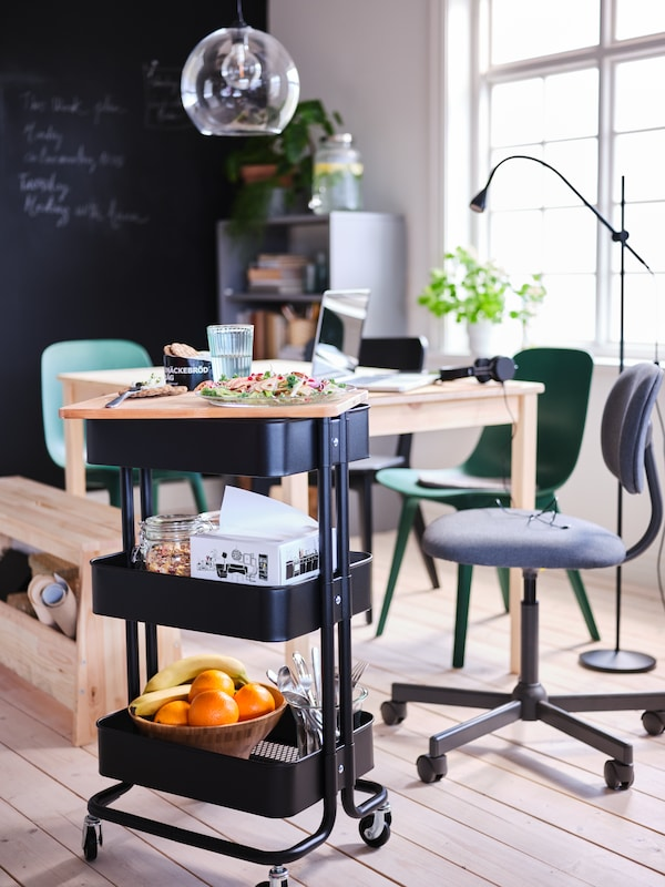 A black RÅSKOG trolley with food and dining accessories beside an INGO pine table with a JAKOBSBYN lamp hanging above.