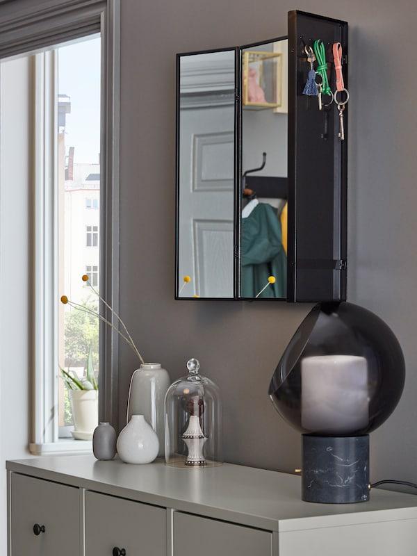 Un espello KARMSUND nunha parede con ganchos por detrás que suxeitan unhas chaves, enriba dunha cómoda BRYGGJA cunha lámpada EVEDAL.