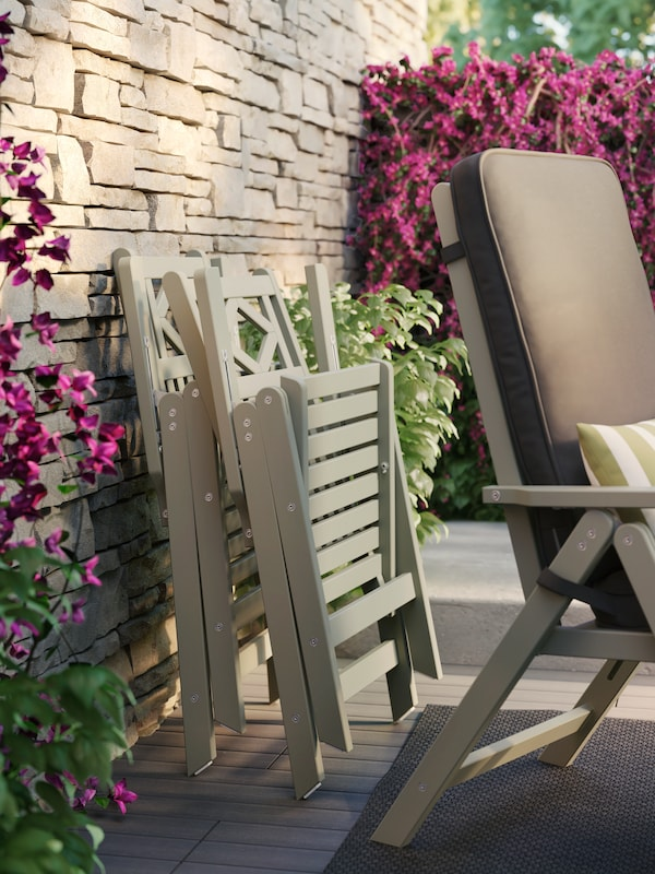 Zwei beigefarbene Stühle lehnen an einer Steinwand mit Weinranken und Grünpflanzen.