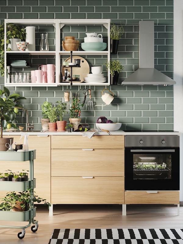 U kuhinji sa svetlozelenim pločicama, na ENHET kuhinjskoj kombinaciji od hrasta, s otvorenim policama, nalaze se posuđe i biljke.