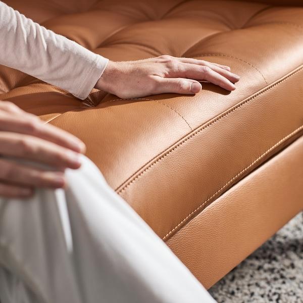 Närbild på en cognacsfärgad lädersoffa där en människa sitter med en hand vilande på soffans sits.