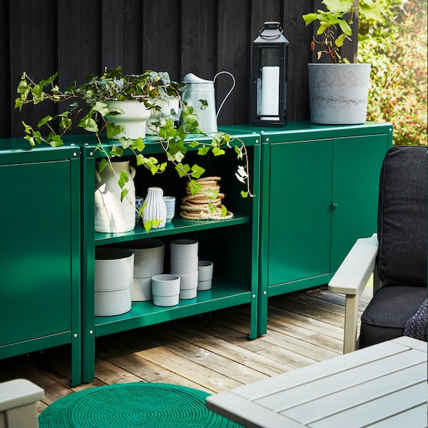 Two outdoor cabinets and one shelving unit in green. Grey pots are stored inside and a watering can and plants are on top.