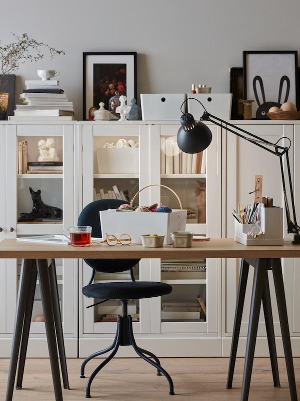 Vor einer Reihe weißer Schränke steht ein Schreibtisch mit einer TERTIAL Arbeitsleuchte, einem TJENA Schreibutensilienfach und Arbeitsutensilien.