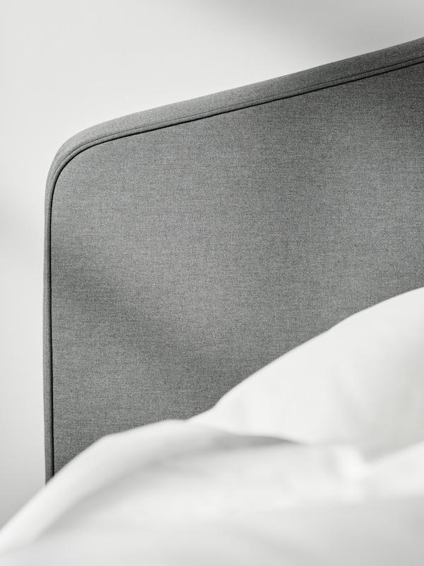 หัวเตียงของเตียงบุนวม HAUGA/เฮากา สีเทาพร้อมผ้านวมและหมอนและผ้าปูที่นอน ÄNGSLILJA/เอ็งส์ลิลยา สีขาวอยู่ถัดไป
