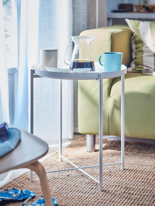 Et hvidt bakkebord med en glaskande med kaffe og to kopper, en gulgrøn sofa og et vævet tæppe.