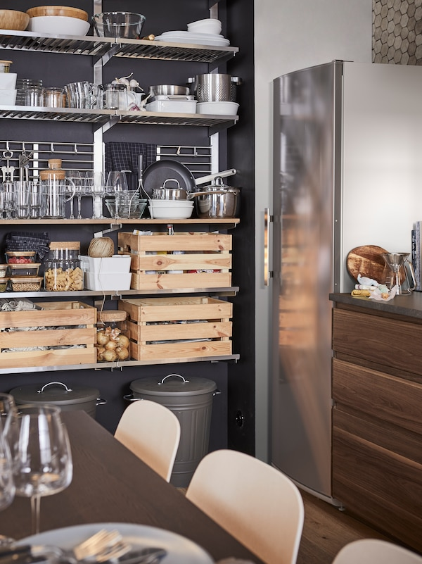 Five stainless steel KUNGSFORS shelving units on a dark grey wall, with crates of food, pots and pans, tableware and jars.