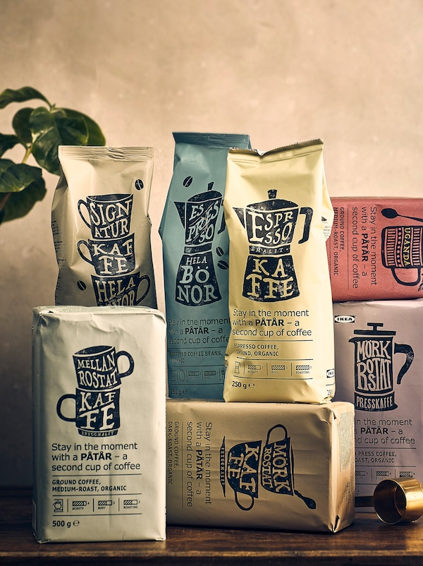 Seven bags of PÅTÅR coffee displayed in a casual manner on a rustic wooden surface. There is a plant in the background.