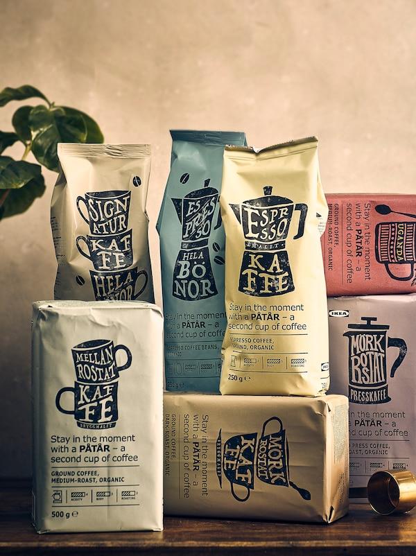 Sieben Beutel PÅTÅR Kaffee auf einer Holzoberfläche. Im Hintergrund ist eine Pflanze zu sehen.