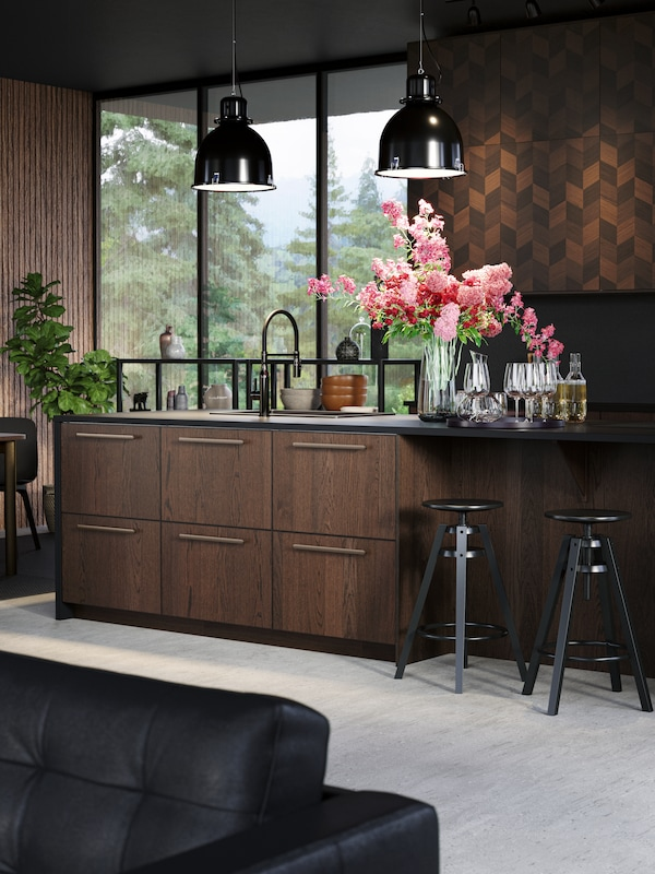 A contemporary kitchen with SINARP drawers and HASSLARP doors, there are two bouquets of red and pink flowers on the worktop.