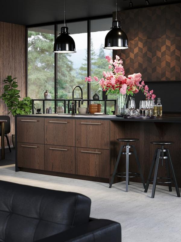 Unha cociña contemporánea con caixóns SINARP e portas HASSLARP con dous ramos de flores vermellas e rosas no mesado.