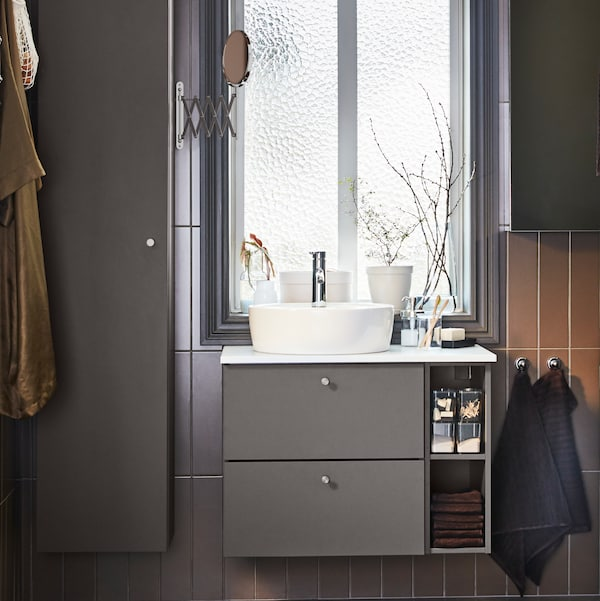 Під вікном з двома навісними шафами з боків – біла раковина на глянцевій сірій/білій шафі під раковину.
