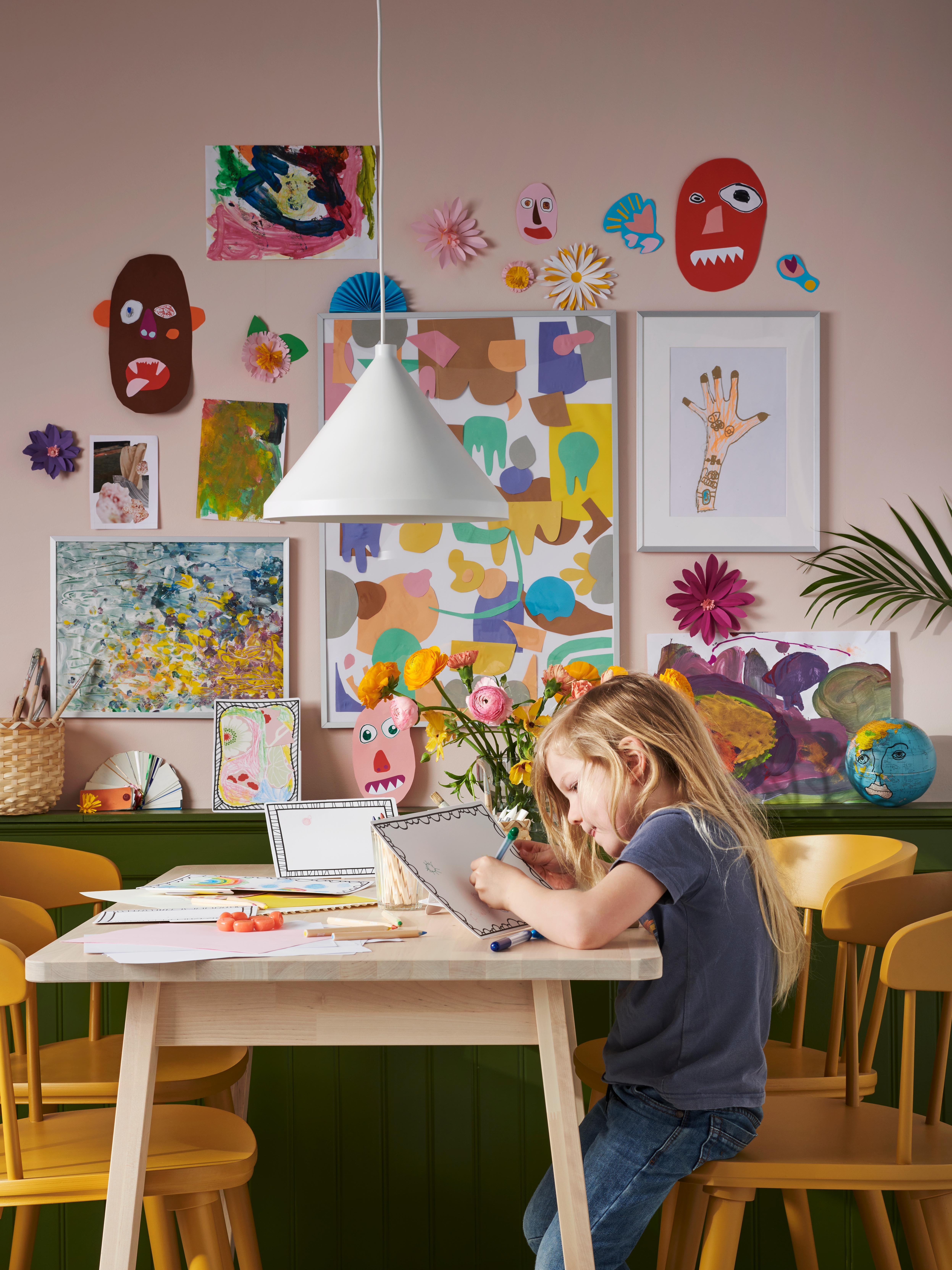 Child drawing on MÅLA framed cardboard at a wooden table with children's artwork in LOMVIKEN frames on wall behind.
