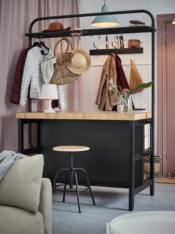 A VADHOLMA kitchen island with rack in black/oak used as a room divider in a hallway and to store clothes and accessories.