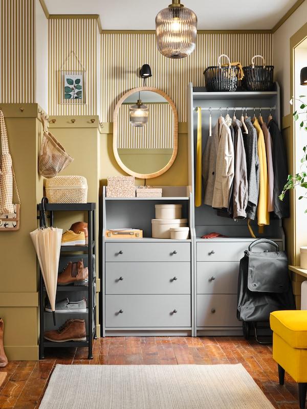 Pomalowany na żółto korytarz z szarą otwartą szafą i komodą HAUGA. Na drążku wiszą ubrania na wieszakach, a na ścianie obok znajduje się lustro.