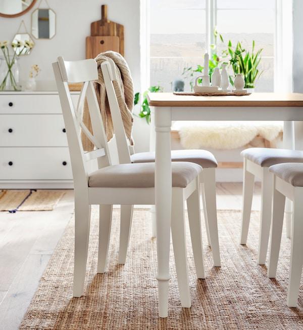 Une grande table brun foncé, huit chaises anthracite, un fauteuil jaune et un buffet avec des portes en bambou.