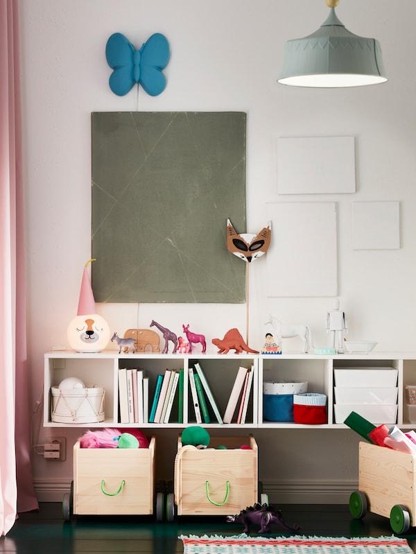 Kerekekkel ellátott FLISAT játéktároló gyerekszobában, SMÅGÖRA polcok alatt, amelyeken könyvek, játékok és dobozok vannak a helyükön.