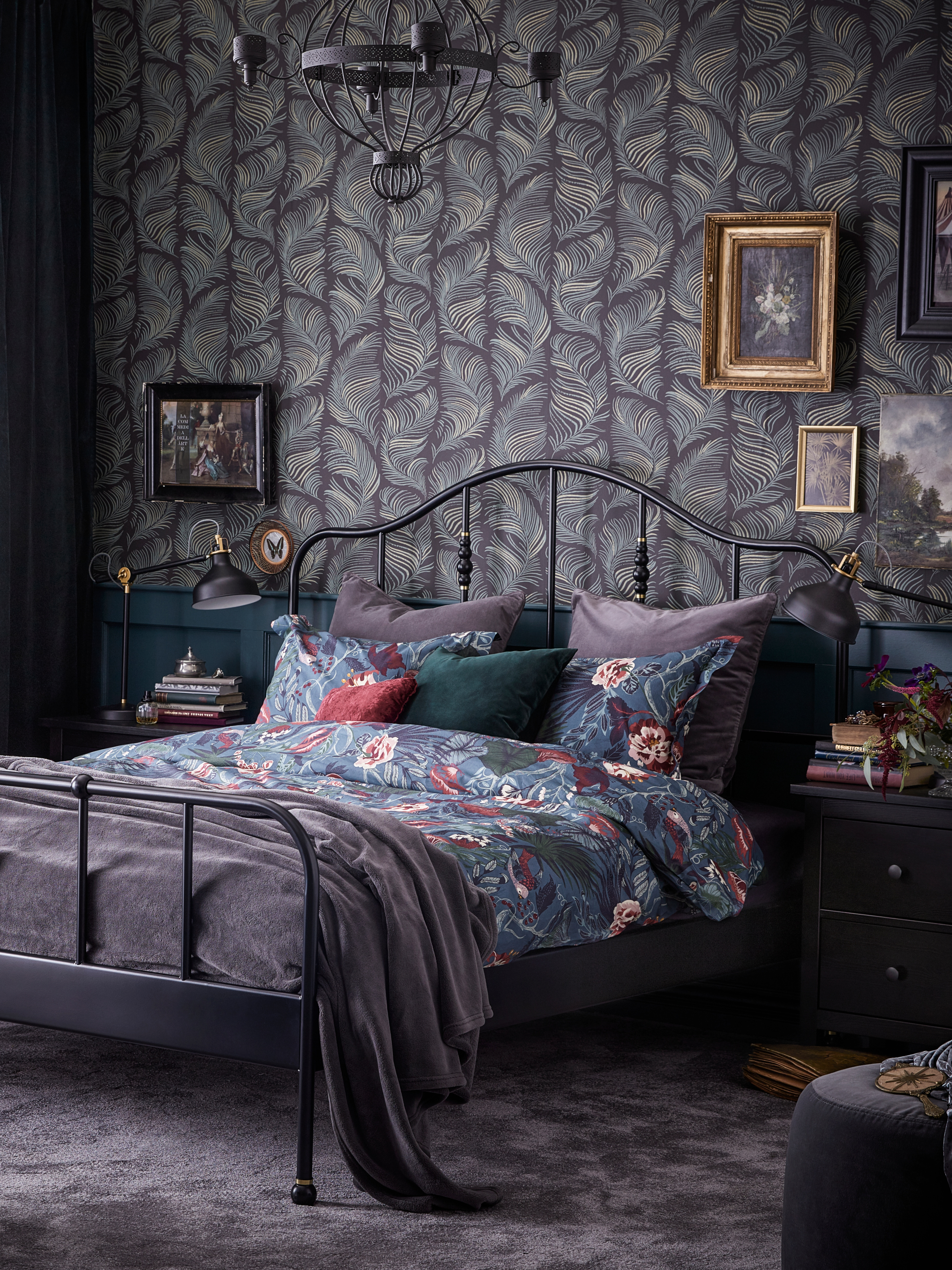 A SAGSTUA black bed frame with a dark blue floral patterned quilt cover is next to a black chest of two drawers in a bedroom.
