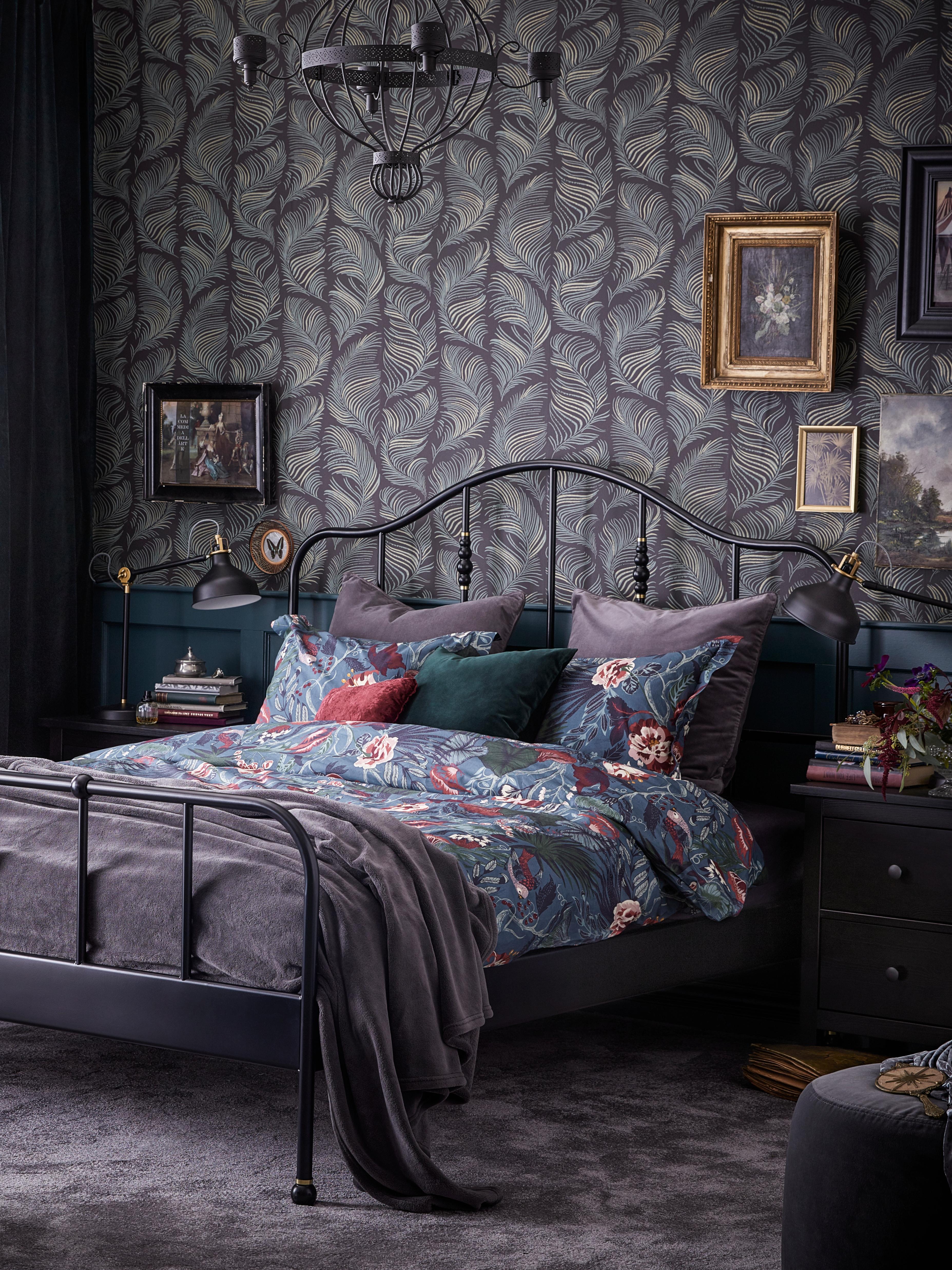 U spavaćoj sobi se nalazi SAGSTUA crni okvir kreveta s tamnoplavom jorganskom navlakom cvetnog dezena pored crne komode s dve fioke.