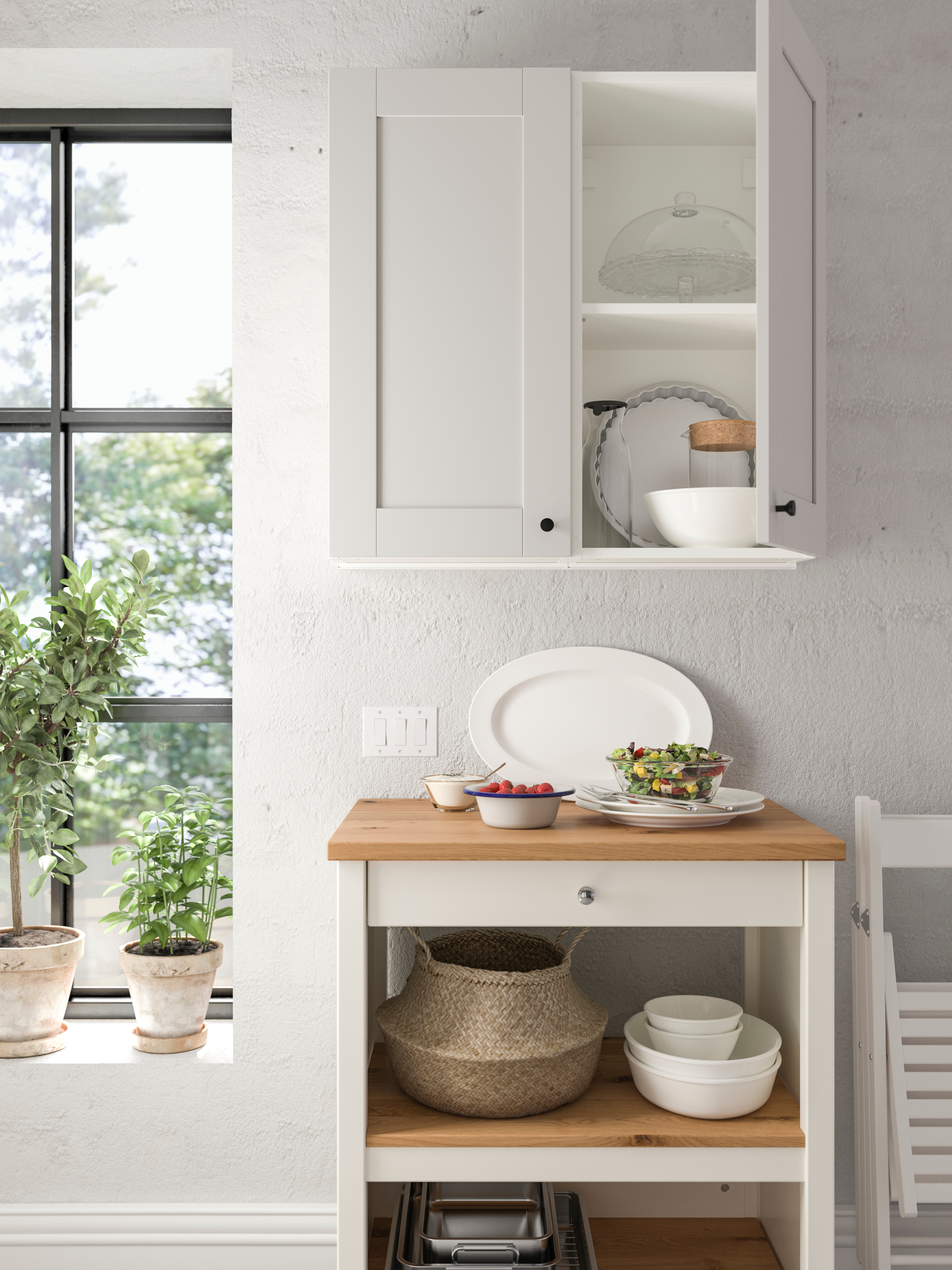 White kitchen with wooden kitchen island, wall cabinet with two doors, basket, serving plate, bowls and dinnerware.