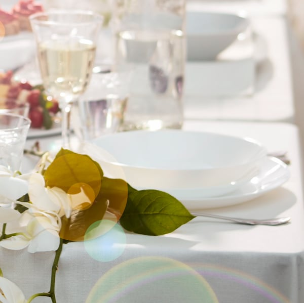 A white OFTAST deep plate stands on top of a white OFTAST plate on a table set with a DYLIK white tablecloth.